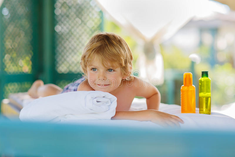 Little kid boy relaxing in spa with having massage stock images