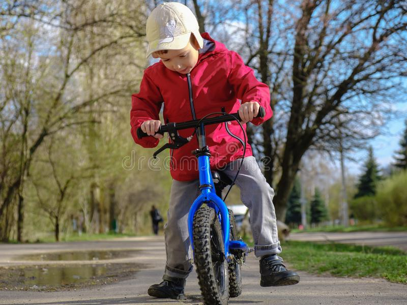 Little kid boy of riding with his first bike in the city park. Happy child in colorful clothes. Leisure for kids outdoors. royalty free stock photo