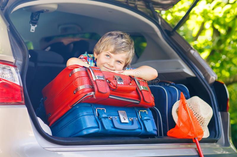 Little kid boy sitting in car trunk just before leaving for vaca stock photography