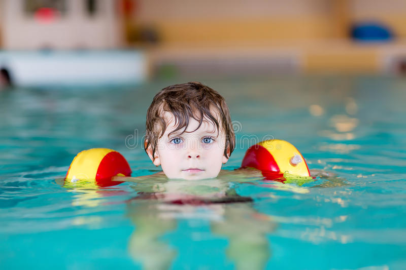 Little kid boy with swimmies learning to swim in an indoor pool royalty free stock image
