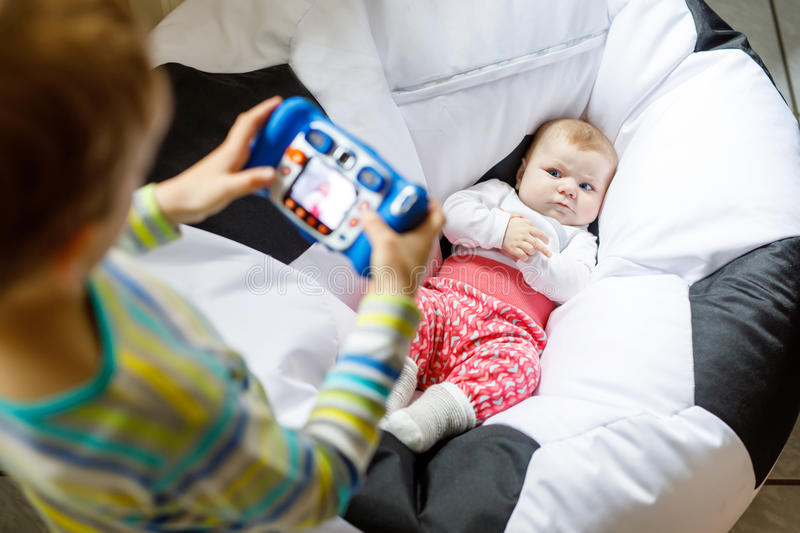 Little kid boy taking picture with toy camera of cute baby girl. royalty free stock photography