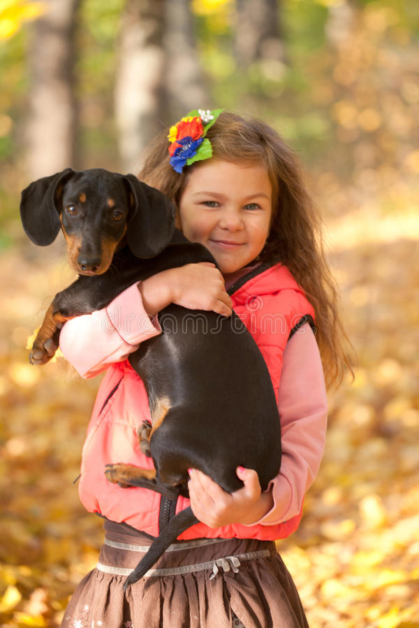 Little kid with dachshund puppy. stock image