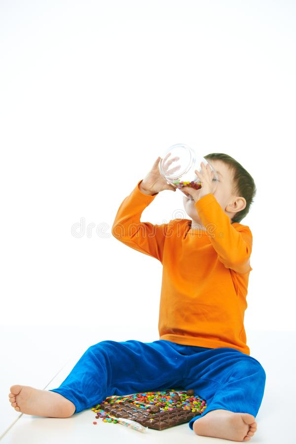 Little kid eating sweets from glass jar at home royalty free stock photos