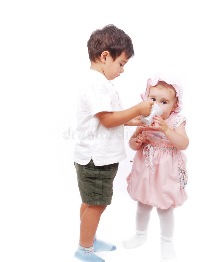 A little kid is feeding his sister. Isolated royalty free stock image