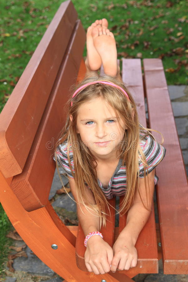 Little kid - girl on a bench. Cute little kid - serious barefoot girl lying on wooden bench stock photos