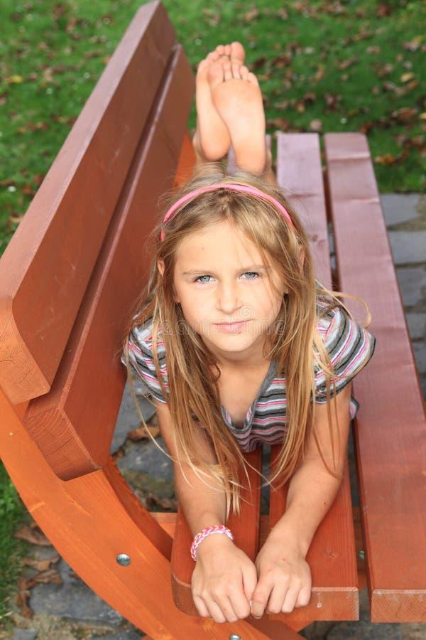 Little kid - girl on a bench stock photos
