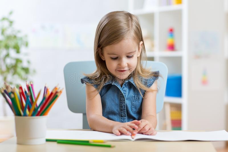 Little kid girl draws sitting at table in room in nursery stock images