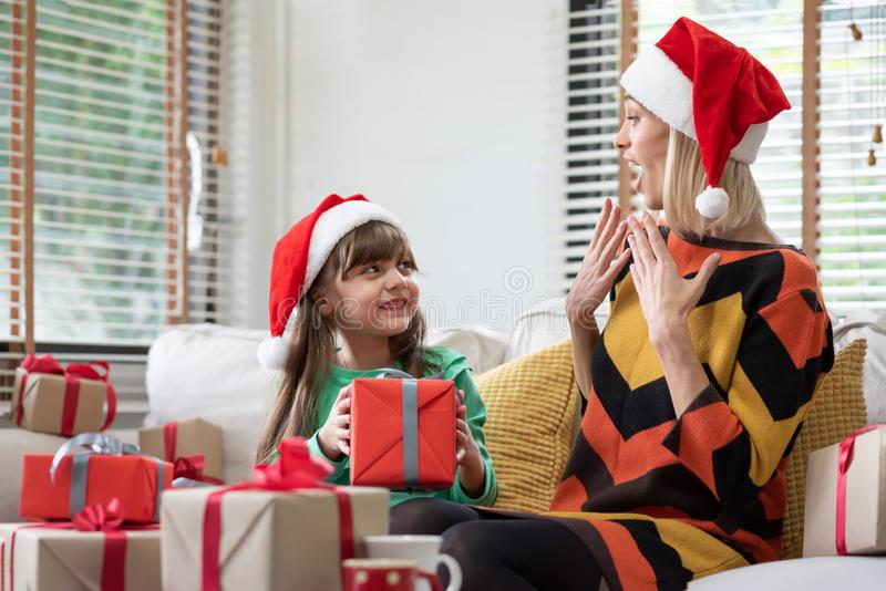 Little kid girl is giving a red gift box for Christmas to her mo stock images