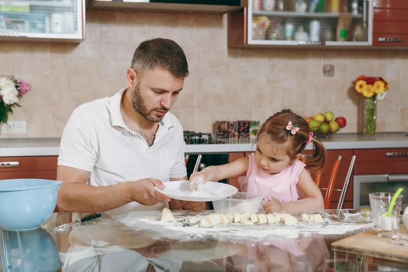 Little kid girl help man to cook lazy dumplings in light kitchen at table. Happy family dad, child daughter cooking food royalty free stock photography