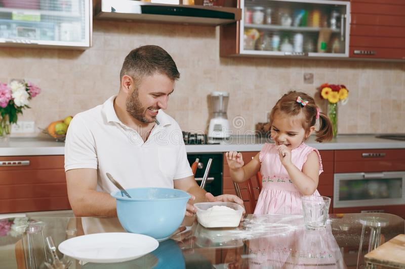 Little kid girl helps man to cook Christmas ginger cookies in kitchen at table. Happy family dad, child daughter cooking royalty free stock photography