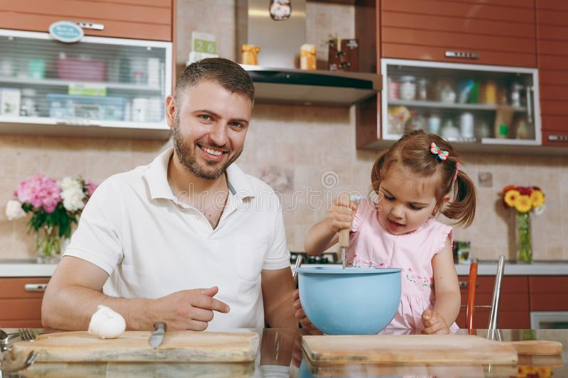 Little kid girl helps man to cook Christmas ginger cookies, stirs eggs, dough in bowl at table. Happy family dad, child stock photography