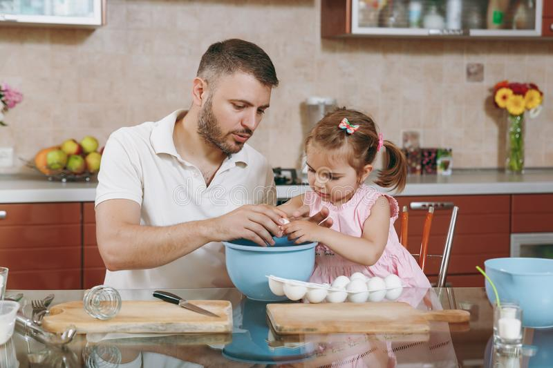 Little kid girl helps man to cook Christmas ginger cookies, breaks egg into bowl at table. Happy family dad, child royalty free stock images