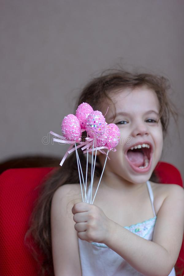 Little kid girl holds pink easter eggs in hands and laugh or smile. royalty free stock photos