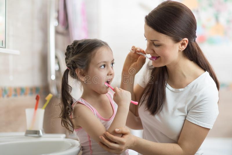 Little child girl and mom brushing teeth in bath - Growing