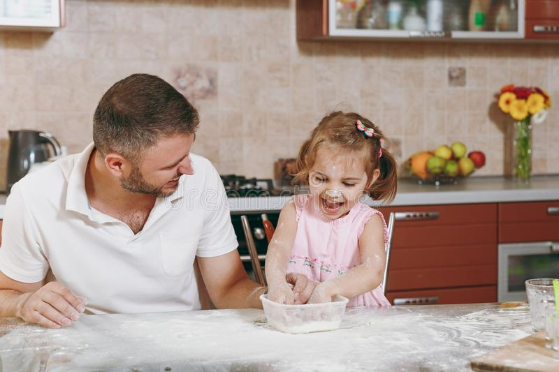 Little kid girl play with man smearing dad with flour in kitchen at table. Happy family dad, child daughter cooking food stock photography
