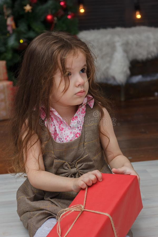 Little kid girl with the red christmas box gift at hands. royalty free stock photo