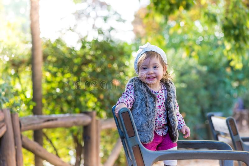 Little kid girl standing in a chair and smiling outdoors stock image
