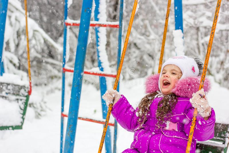 Little kid girl swinging on the winter park. royalty free stock images