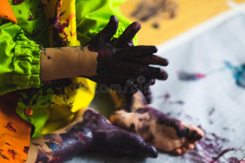 Little kid hands and feet covered with multiple colours. Chlid playing with different color paintings ends with multicolor hands and feet stock photo