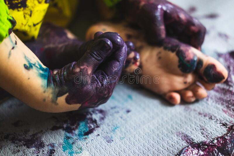 Little kid hands and feet covered with multiple colours. Chlid playing with different color paintings ends with multicolor hands and feet royalty free stock photos