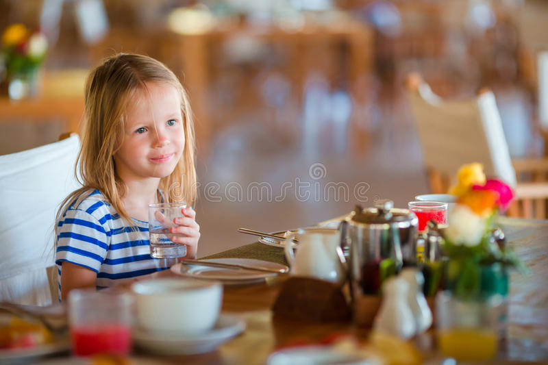 Little kid having breakfast at outdoor cafe. Adorable girl drinking fresh watermelon juice enjoying breakfast. Adorable little girl having breakfast at resort stock images