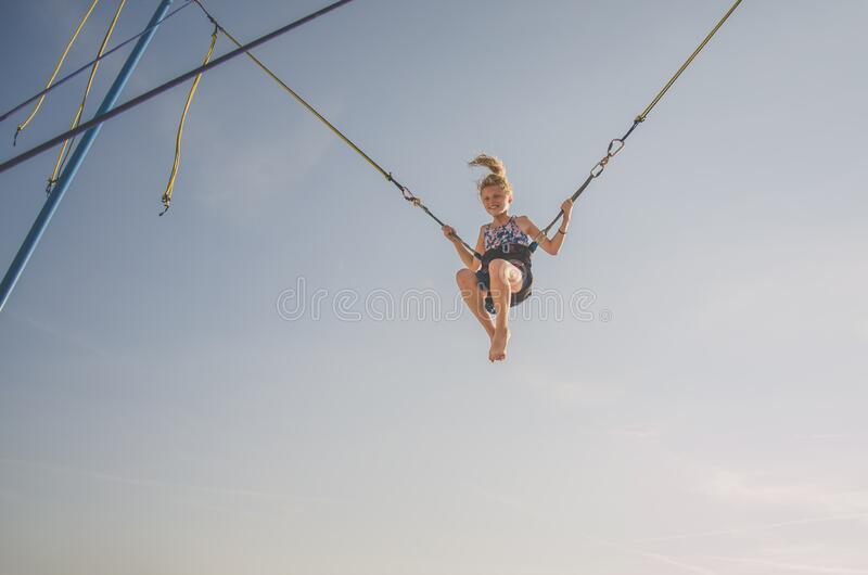 Lovely blond caucasian girl jumping in the jump attraction in the playground. Little kid having fun in the bungee jumping attraction flying high into the blue stock images