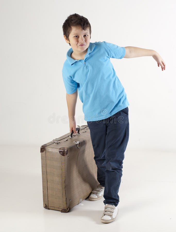 Little kid with heavy suitcase stock photography