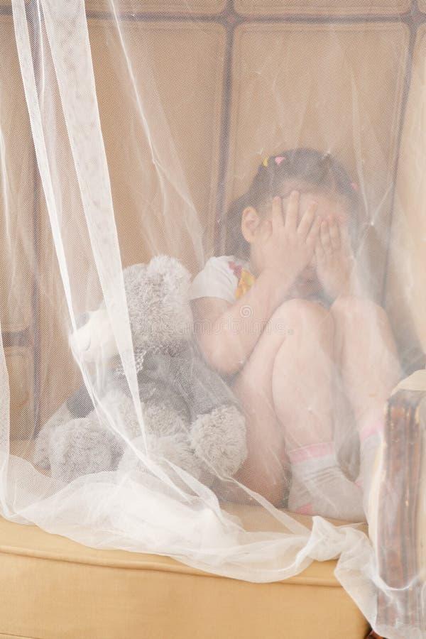 Little kid hiding behind teddy bear royalty free stock photos