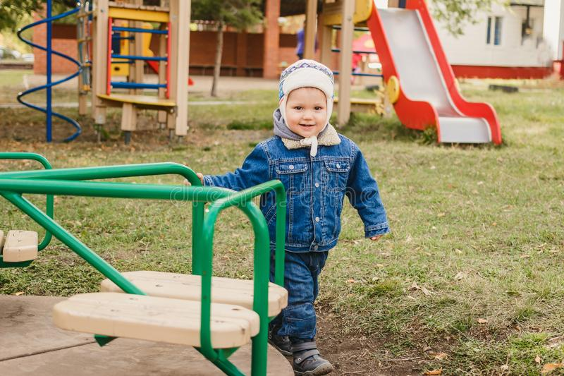 Little kid in jeans suit plays on the playground, boy spinning on the carousel. Little kid in jeans suit plays on the playground, happy boy spinning on the royalty free stock photos