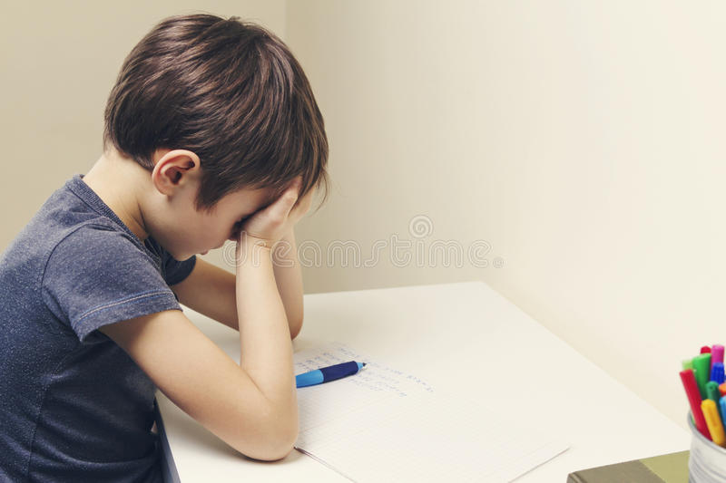Little kid made his homework at home. The boy is tired and covers his face with hands. Tired child doing homework at home. The boy fed up and covers his face stock images