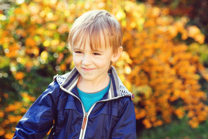 Little kid playing in the autumn on the nature walk. Smiling little boy outdoors portrait. Happy childhood stock photos