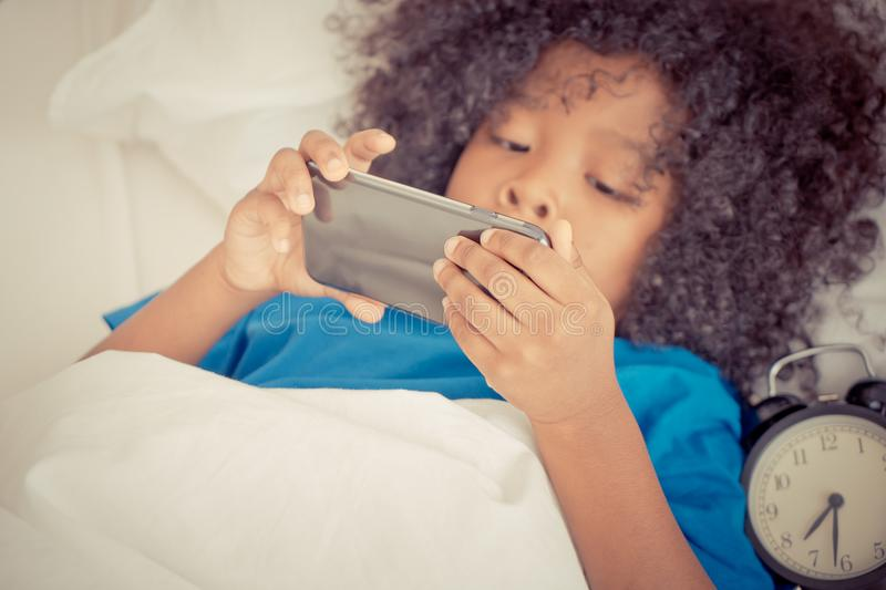 Little kid playing with mobile phone on bed with alarm clock stock photo