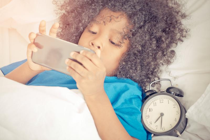 Little kid playing with mobile phone on bed with alarm clock royalty free stock photo