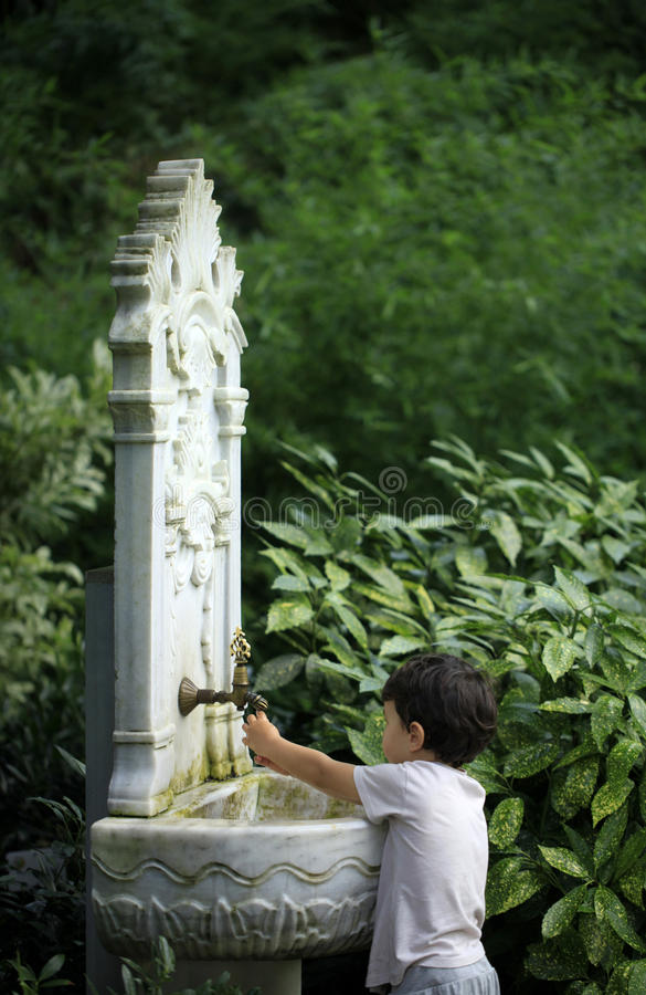 Little kid playing with water from Ottoman style classic fountain royalty free stock image