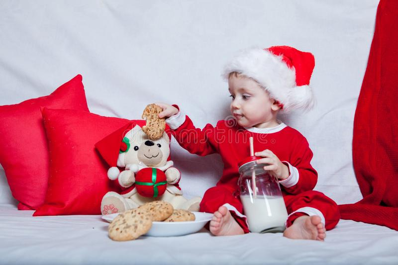 A little kid in a red cap eats a cookies and milk. Christmas photography of a baby in a red cap. New Year holidays and Christmas royalty free stock image