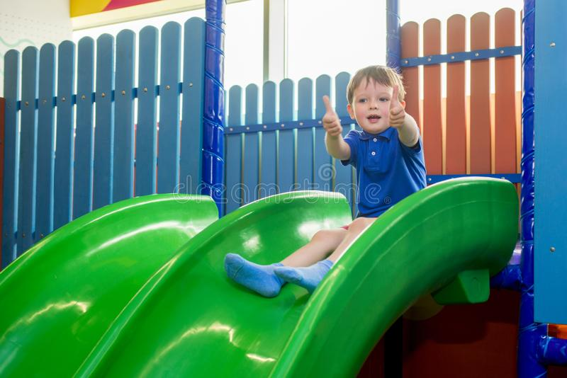 Little kid riding from childrens slides in game center and shows thumbs up. Happy little kid, children riding up, down on slide, i stock photos