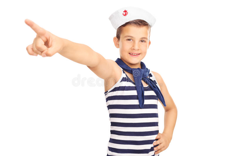 Little kid in a sailor costume pointing forward. Studio shot of a little male kid in a sailor costume pointing forward with his hand and looking at the camera stock photo
