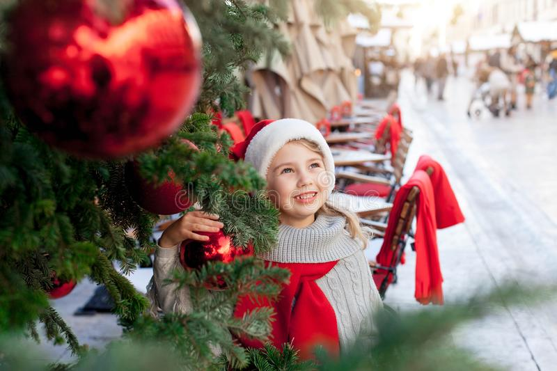 Little kid in santa hat at winter market near street cafe in old town. Cozy festive and New Year. Child girl is smiling under Christmas tree with red ornaments royalty free stock images