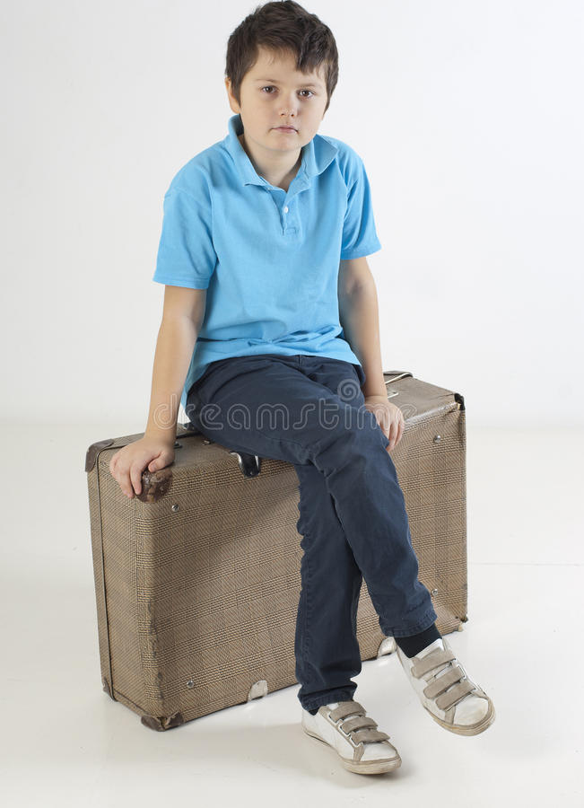 Little kid siting on a suitcase royalty free stock photography