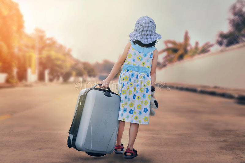 A little kid with a suitcase escape from house stock photography