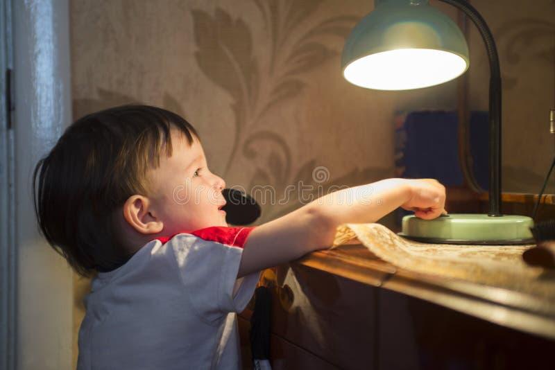 Little kid turning off the light stock photo