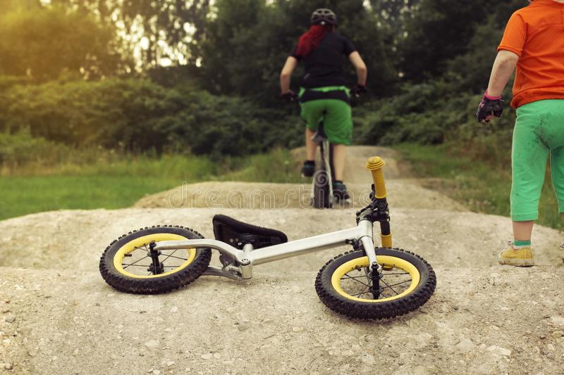 Little kid watching her red haired mom riding a bike on a pumptrack with excitement, balance bike lying on the ground royalty free stock photo