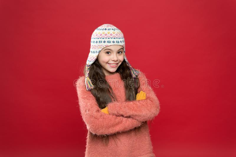 Little kid wear knitted hat. Little girl winter fashion accessory. Small child long hair wear hat red background royalty free stock image