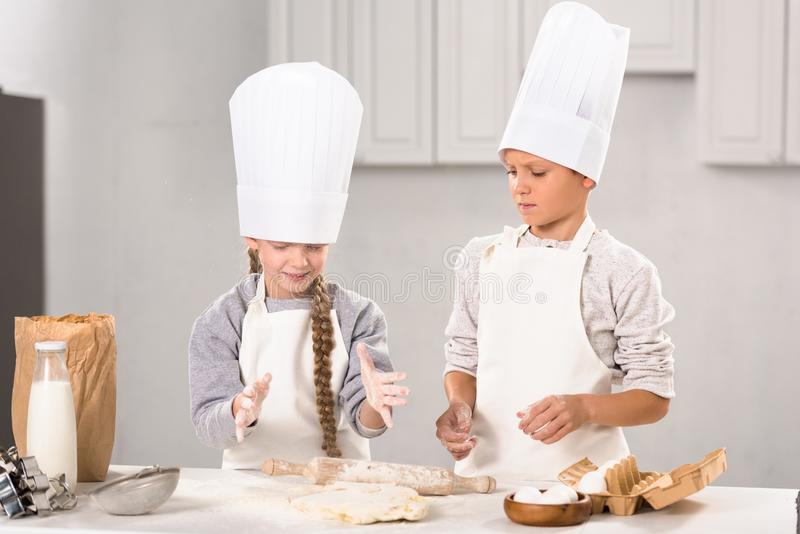 Little kids in aprons and chef hats making dough with rolling pin at table. In kitchen royalty free stock photo