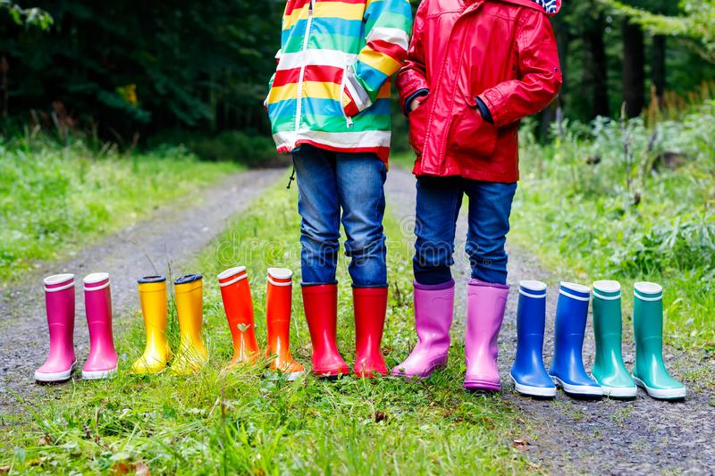 Little kids, boys and girls in colorful rain boots. Children standing in autumn forest. Close-up of schoolkids and stock photo