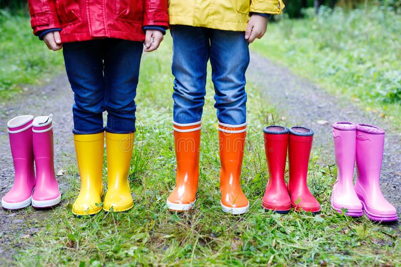 Little kids, boys and girls in colorful rain boots. Children standing in autumn forest. Close-up of schoolkids and royalty free stock image