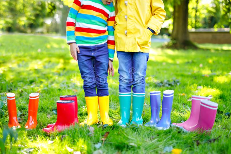 Little kids, boys and girls in colorful rain boots. Close-up of children in different rubber boots, jeans and jackets stock images