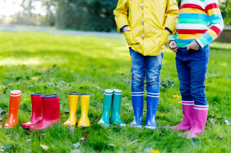 Little kids, boys or girls in jeans and yellow jacket in colorful rain boots stock photography
