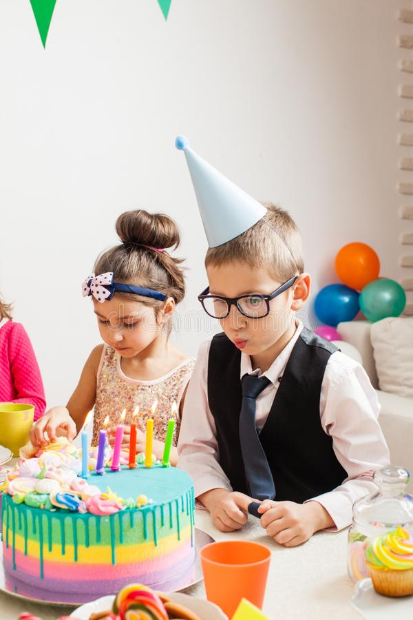 Desire on birthday. Little kids celebrating birthday. The boy blown candles on the cake royalty free stock images