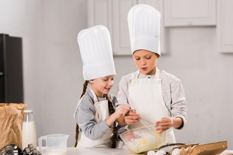 Little kids in chef hats and aprons whisking eggs in bowl at table. In kitchen stock images